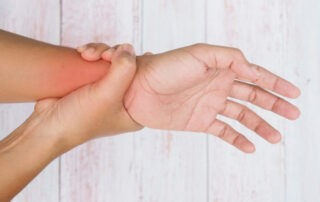 A person holding their wrist in pain signaling a hand injury